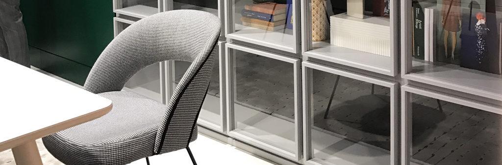 Vackra, luftiga detaljer på fåtölj och bokhylla i grått.